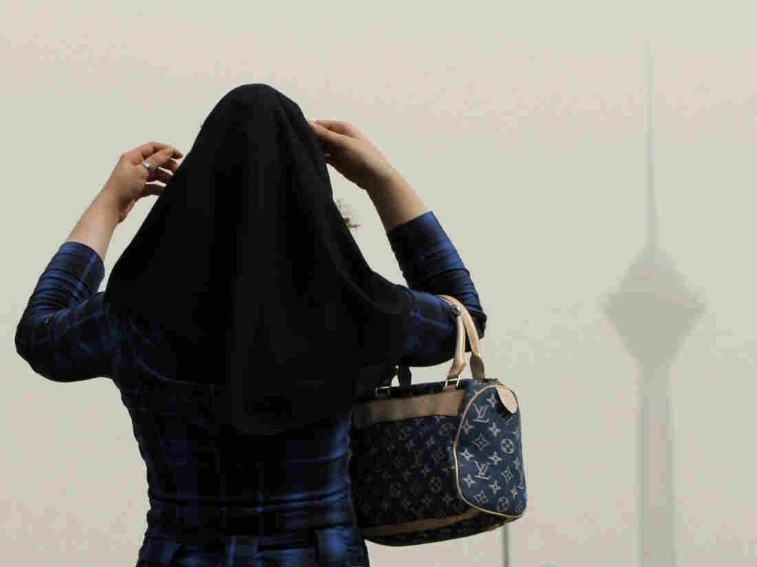 In Tehran, a woman adjusts her headscarf.