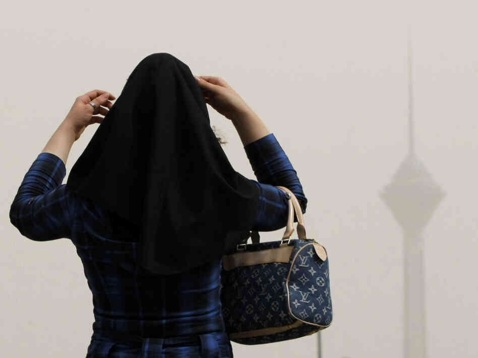 In Tehran, a woman adjusts her headscarf.