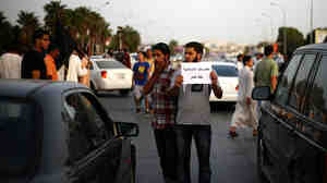 """A Libyan follower of Ansar al-Sharia Brigades carries a placard reads in Arabic """"our Islamic holies are red line,"""" during a protest in front of the Tibesti Hotel, in Benghazi, Libya, on Sept. 14, as part of widespread anger across the Muslim world about a film ridiculing Islam's Prophet Muhammad."""
