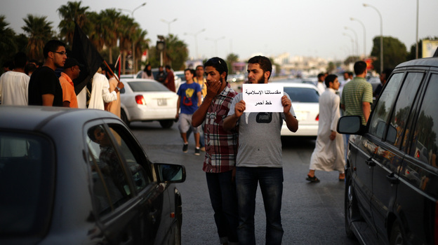 """A Libyan follower of Ansar al-Sharia Brigades carries a placard reads in Arabic """"our Islamic holies are red line,"""" during a protest in front of the Tibesti Hotel, in Benghazi, Libya, on Sept. 14, as part of widespread anger across the Muslim world about a film ridiculing Islam's Prophet Muhammad. (AP)"""