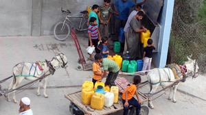 Palestinians fill their bottles with potable water at a water purification station in Deir al-Balah, central Gaza Strip, in July. About 95 percent of the municipal water is undrinkable, and only about 40 percent of homes have access to potable water on a regular basis.