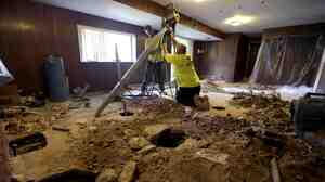 Contractors drive piers into the ground to stabilize a settling home in Manchester, Mo. on Aug. 29, 2012.