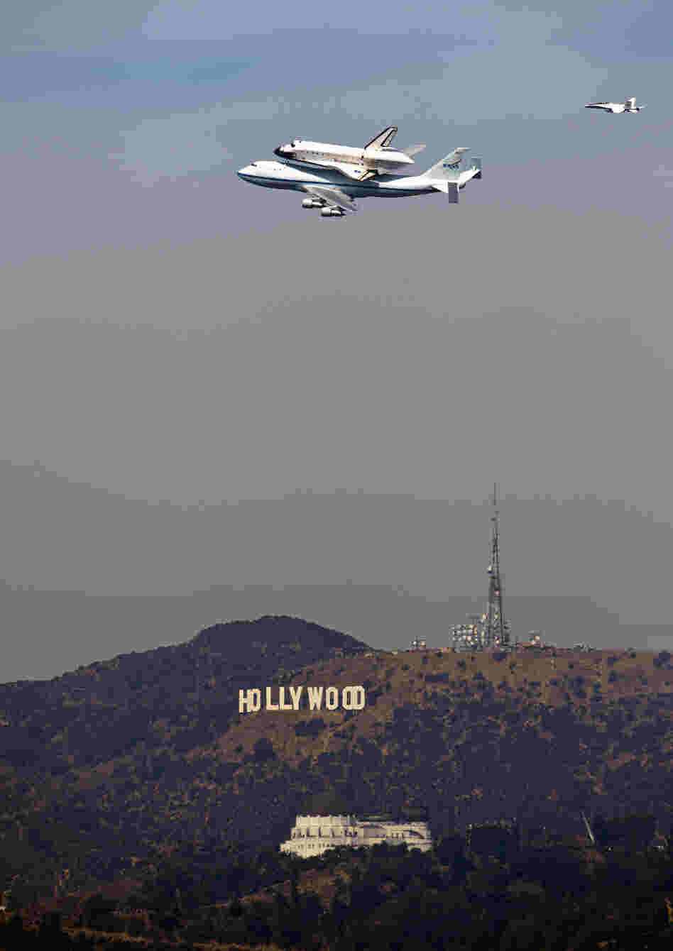 The Space Shuttle Endeavour passes the Hollywood Sign and the Griffith Observatory as seen from Dodger Stadium Friday.