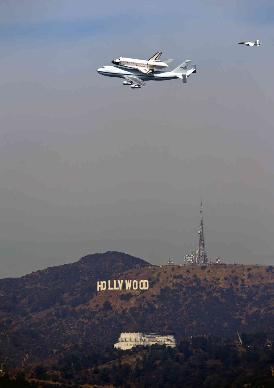 The Space Shuttle Endeavour passes the Hollywood Sign and the Griffith Observatory as seen from