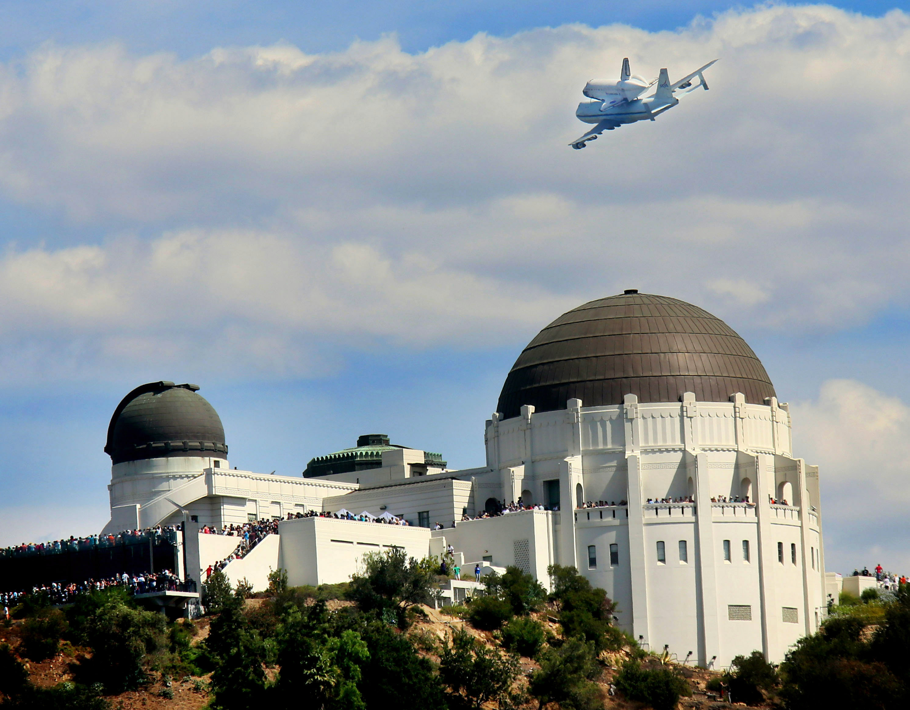 The space shuttle Endeavour flies atop NASA's Shuttle Carrier Aircraft or SCA over the Griffith Park Obervatory in Los Angeles.