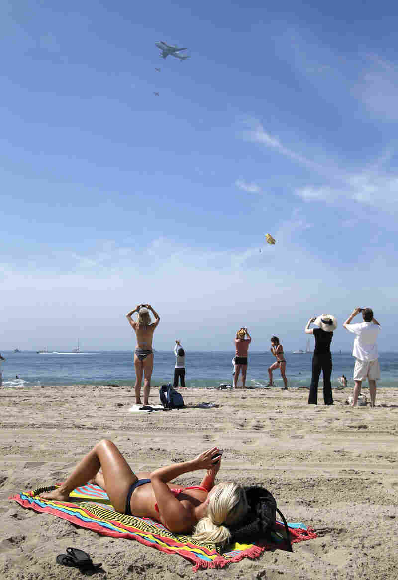 Spectators take pictures with varied levels of excitement, as the Space Shuttle Endeavour, mounted on NASA's Shuttle Carrier Aircraft, flies near Santa Monica.