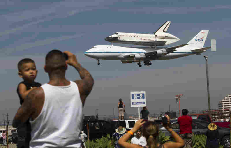 Spectators Mario Vasquez of Redondo Beach and his son Mario Jr., 2, watch as Endeavour prepares to land at Los Angeles International Airport Friday. In a few weeks, the shuttle will travel through the city's streets to its new home at the California Science Center.
