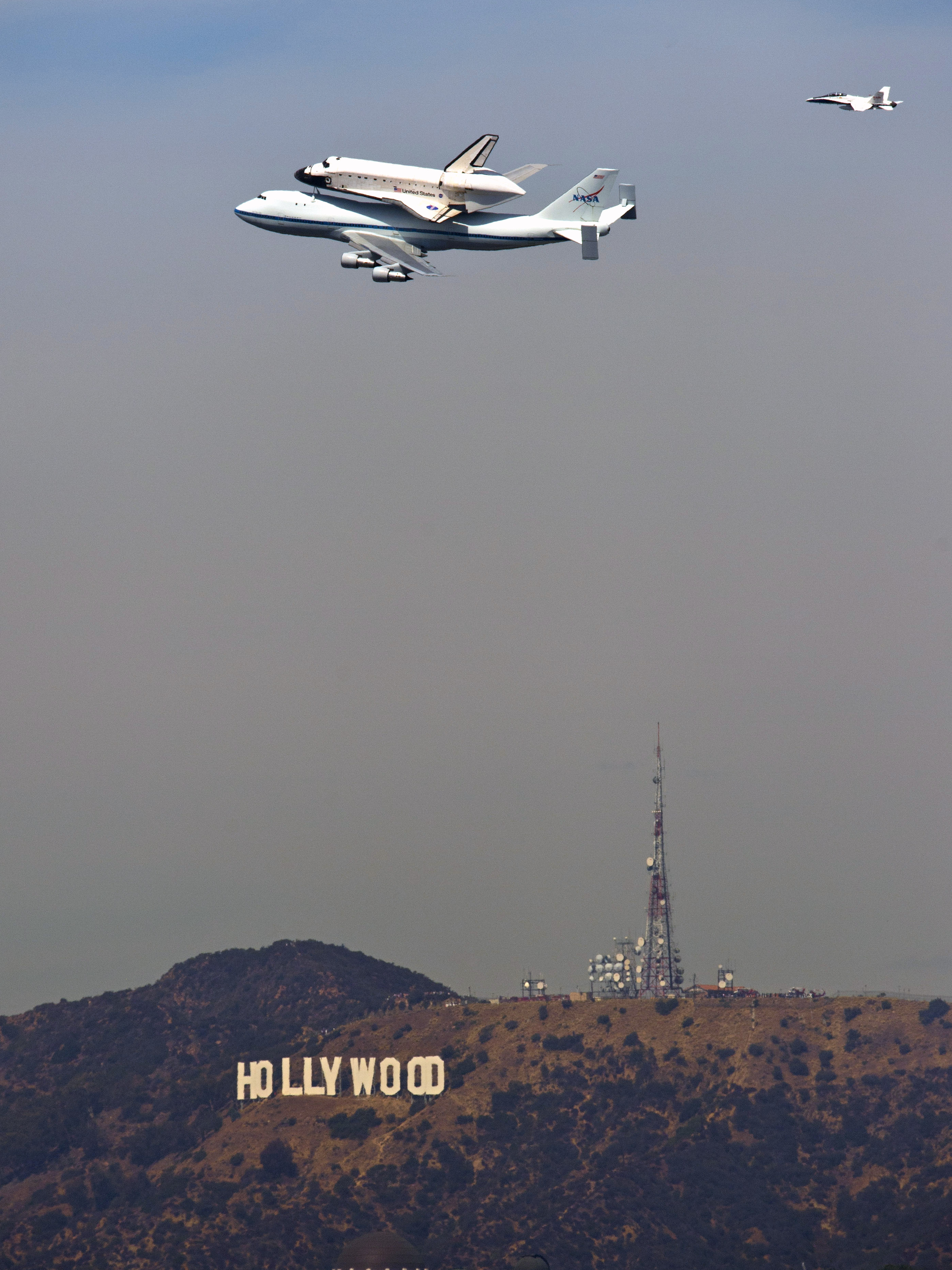 The Space Shuttle Endeavour atop a modified 747 passes the Hollywood sign and the Griffith Observatory as seen from Dodger Stadium Friday.