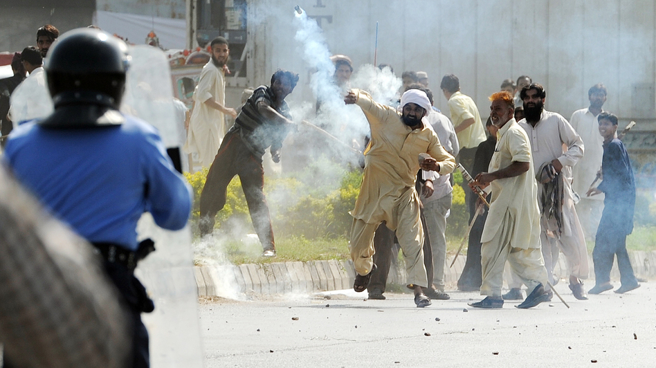 In Islamabad today, this demonstrator threw a tear gas canister back toward police.