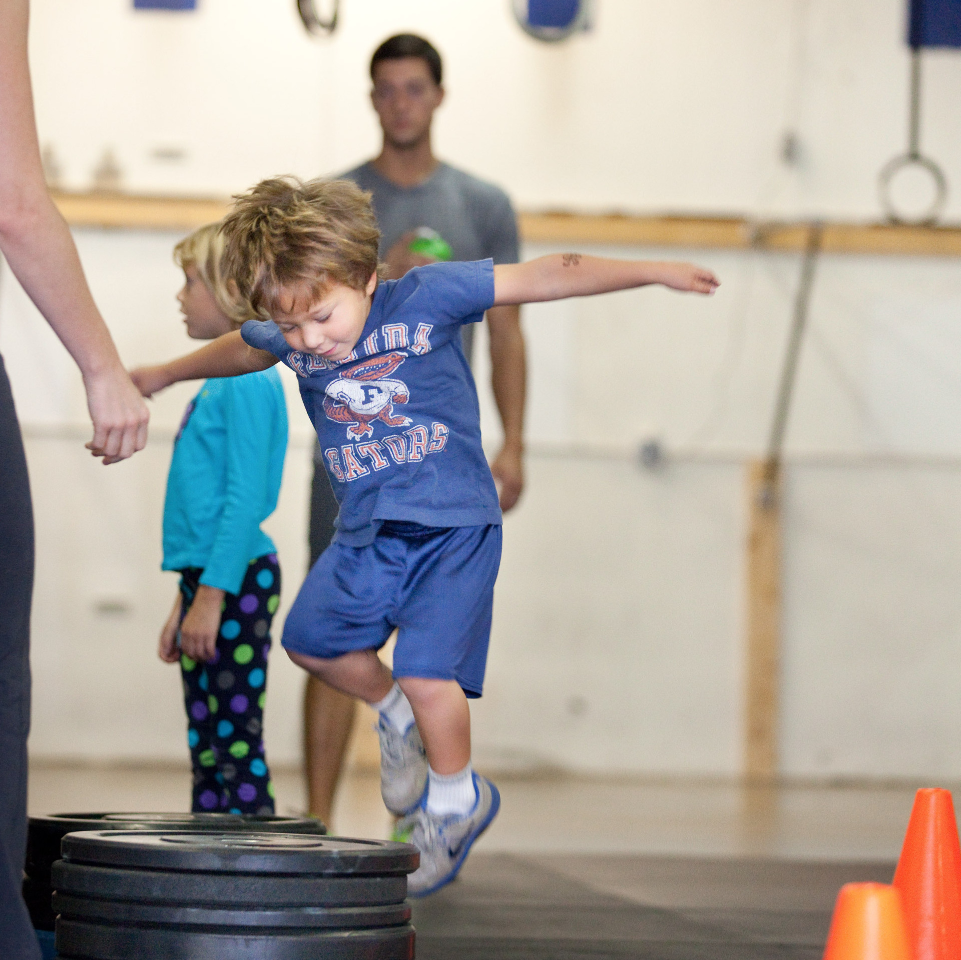 Evan Ciangiulli, 4, hops onto a stack of weights as part of his CrossFit training in Rockville, Md.