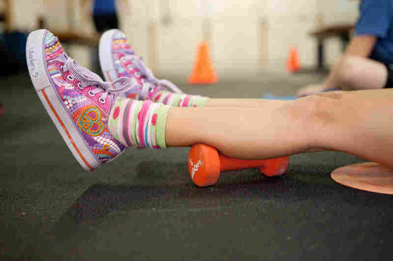 Simara Decker, 6, relaxes before beginning her weightlifting exercise.