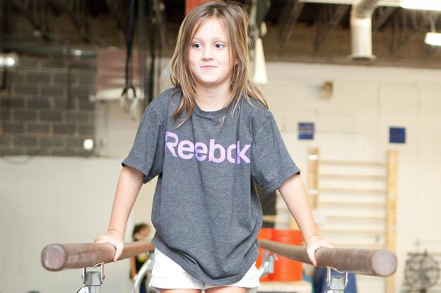 Simara Decker, 6, practices on the parallel bars.