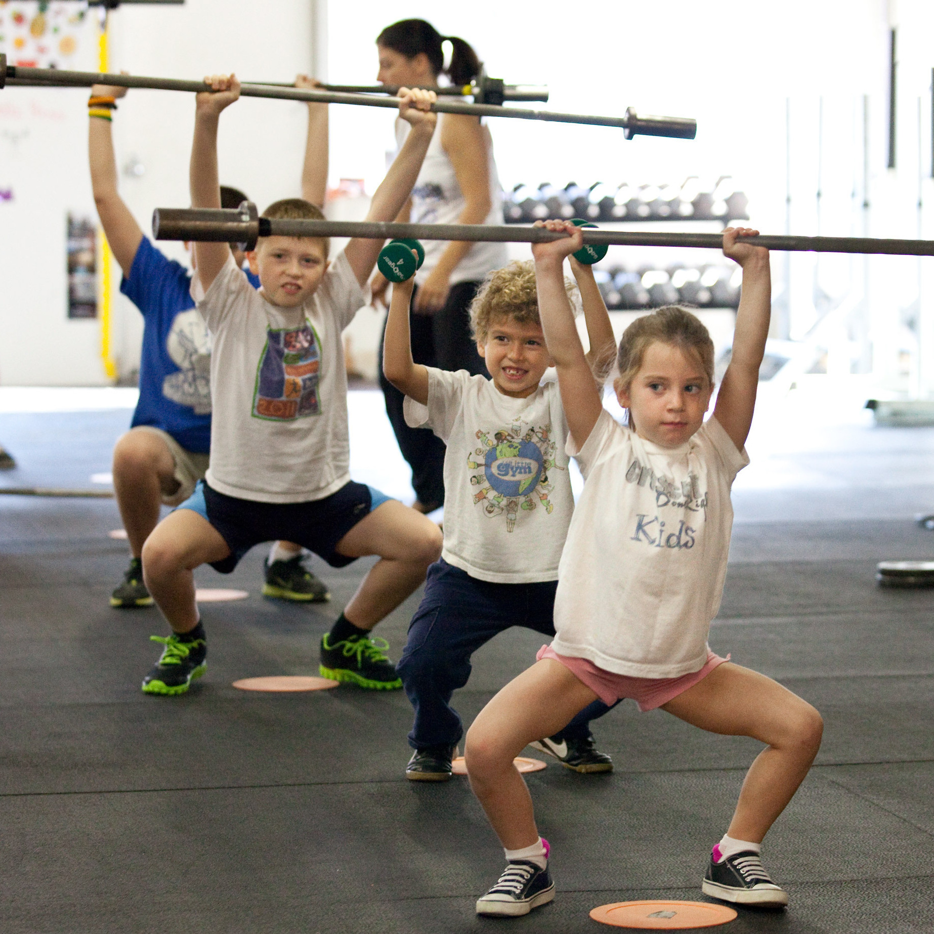 Six-year-old Rose MacDormett (front) lifts a barbell as part of a CrossFit class for children at CrossFit DoneRight in Rockville, Md.