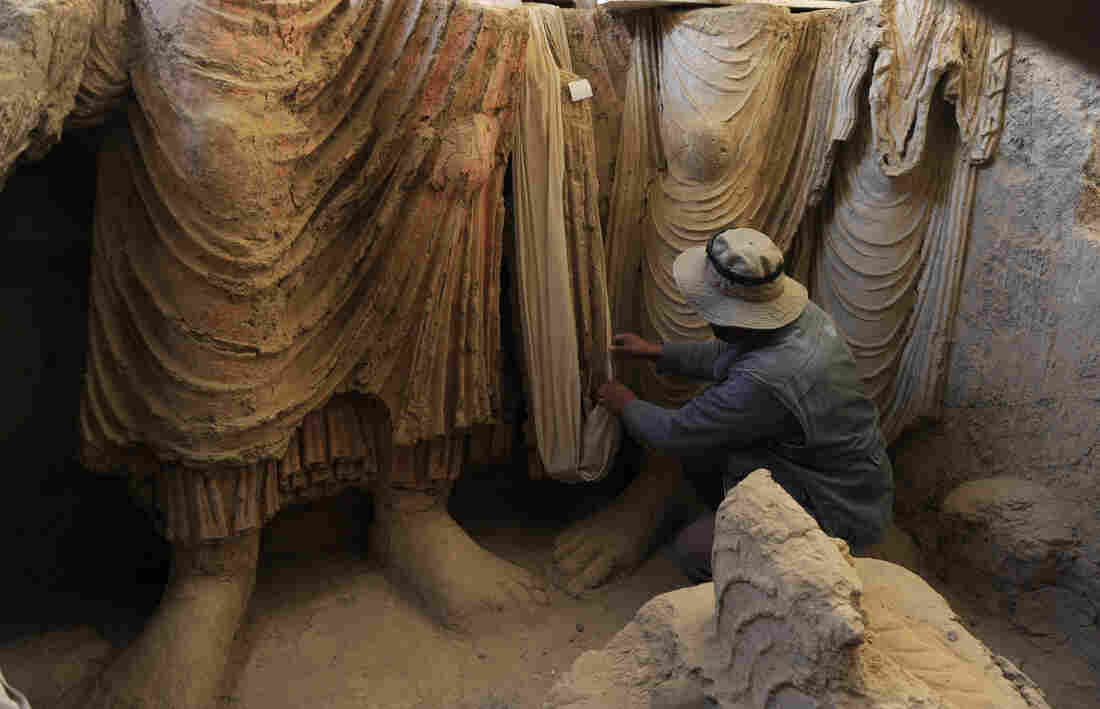 Above, an Afghan archaeologist drapes a fabric across the remains of Buddha statues discovered inside an ancient monastery in Mes Aynak on Nov. 23, 2010.