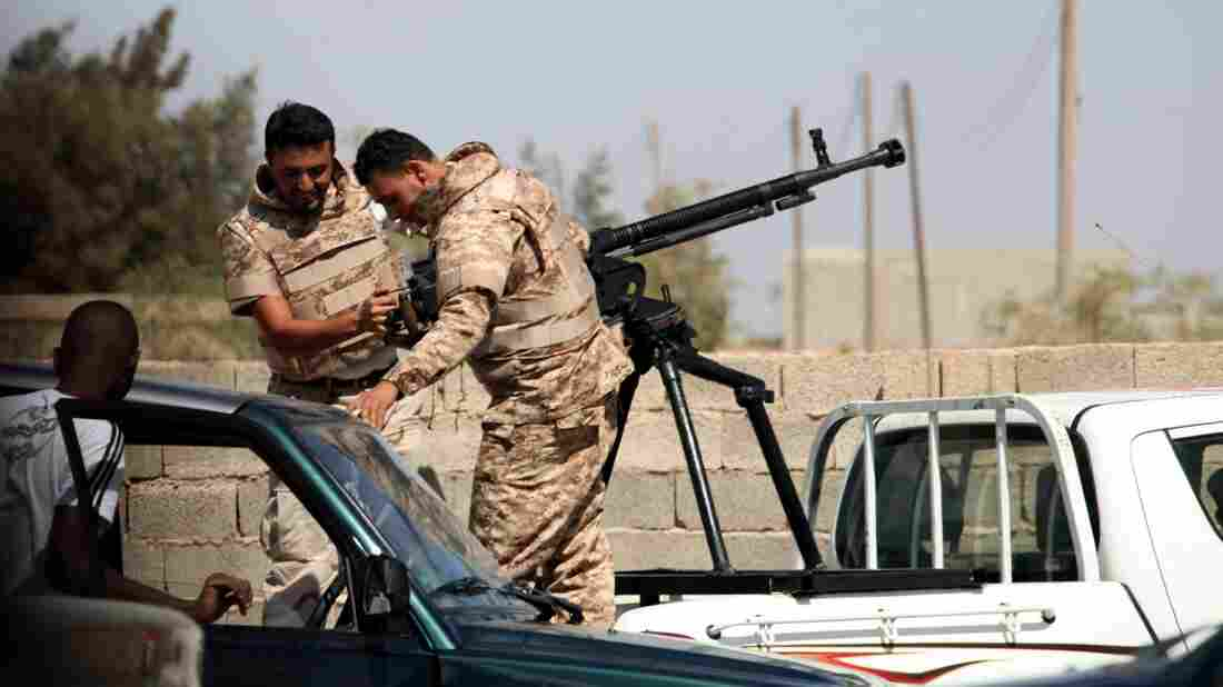 Soldiers from the Libyan National Army get ready to enter the compound of Rafallah al-Sahati in Benghazi on Saturday. Libya's president announced that all government-aligned militias will now report to the army chief of staff, and that all other armed groups must disband.