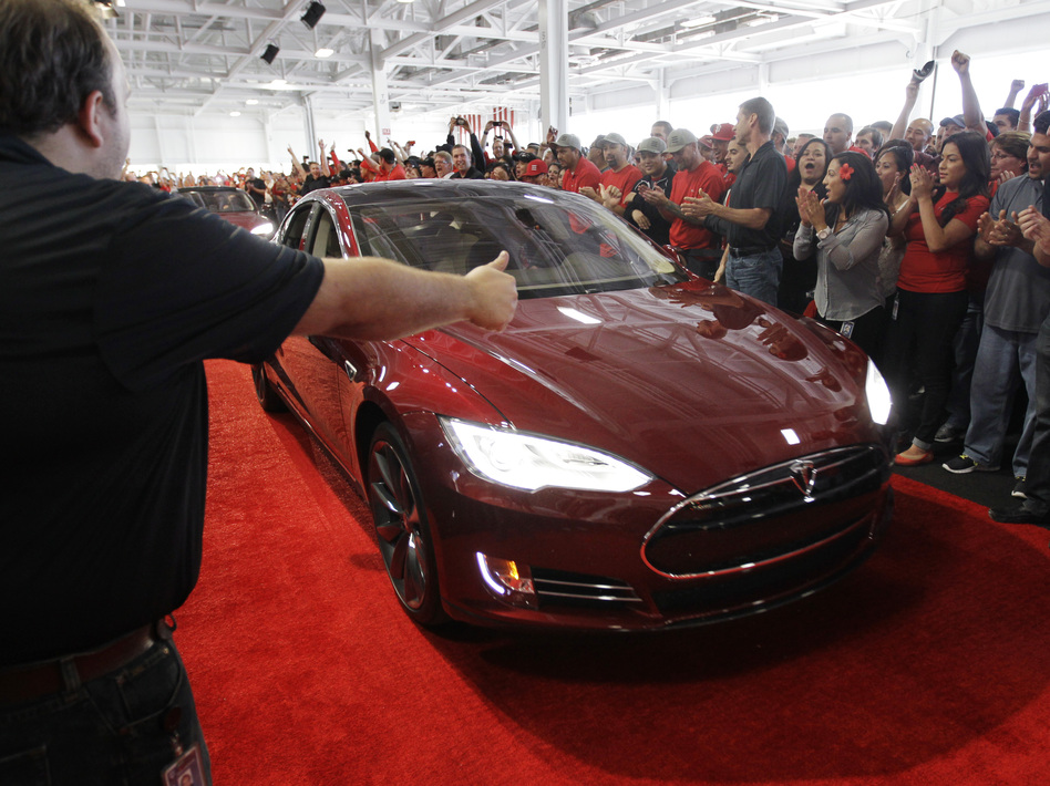 Tesla workers cheer on one of the first Tesla Model S cars sold, during a rally at the Tesla factory in Fremont, Calif., in June. The company is now unveiling a new network of refueling stations for the vehicles. (AP)