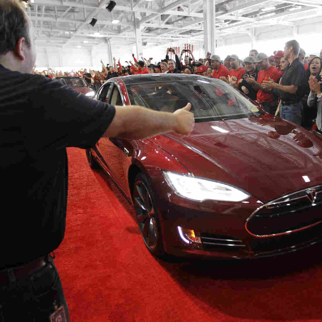 Tesla workers cheer on one of the first Tesla Model S cars sold, during a rally at the Tesla factory in Fremont, Calif., in June. The company is now unveiling a new network of refueling stations for the vehicles.