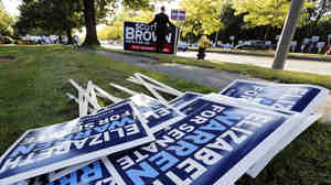 Bill Connell of Weymouth, Mass., who supports Republican Sen. Scott Brown, stands near signs supporting Brown's Democratic challenger, Elizabeth Warren, before the candidates' first debate Thursday in Boston.