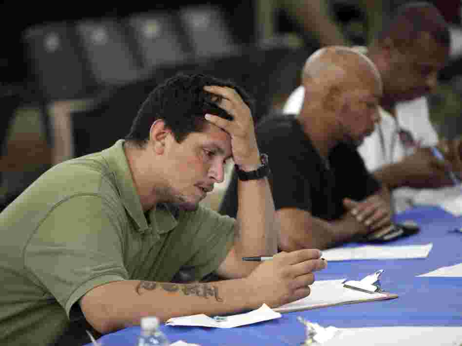 Job seekers fill out applications Aug. 21 at a construction job fair in New York. Polls show voters want the presidential candidates to provide more details on how they would reduce unemployment, change tax policy and alter government spending.