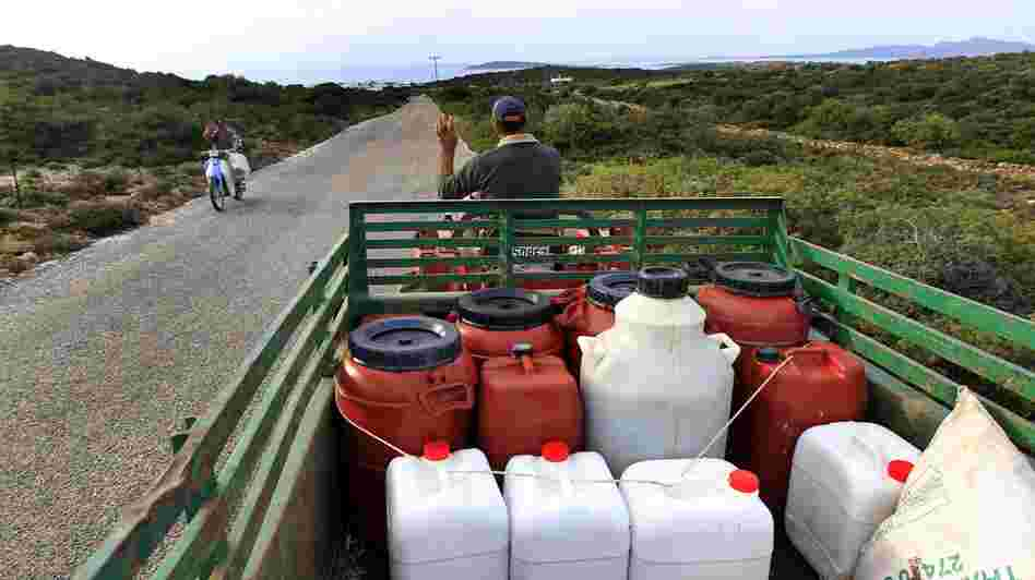 A Greek farmer drives home with his fresh pressed olive oil in barrels near Alyki, Greece. The country's pure olive oil is hard to find, expensive and poorly marketed, businessmen say.
