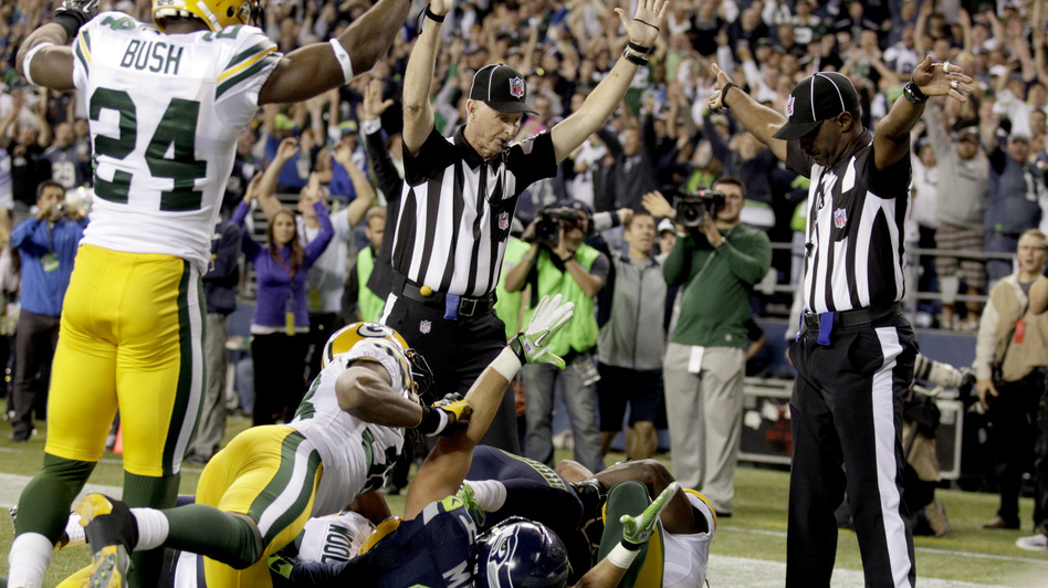 Confusion: One official (to the  left) signals touchdown for Seattle. The other signals that a touchback — possession — for Green Bay. (AP)