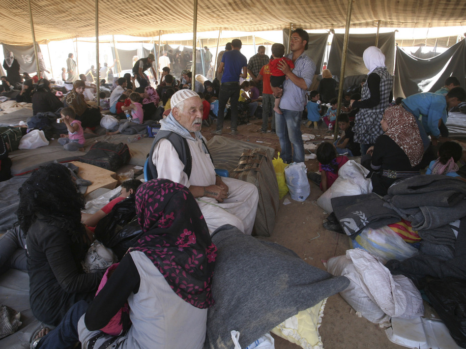 Newly arrived Syrian refugees gather at Zaatari camp, in Mafraq, Jordan, Aug. 29. Residents have rioted over the poor living conditions at the camp. The Jordanian government is not allowing Syrians to leave the camp and join friends or family elsewhere in the country. (AP)