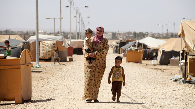 A Syrian refugee walks with her ch