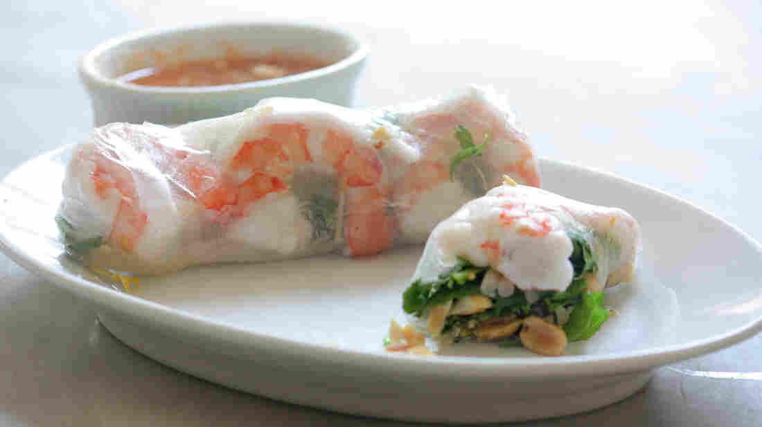 A Classic Summer Roll with shrimp on a plate, with a bowl of dipping sauce in the background