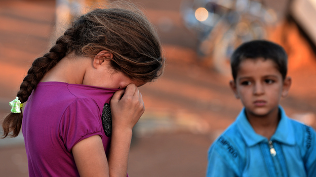 A young Syrian girl wiped her tears after not being allowed entry to Turkey last month. Thousands of Syrians have fled to neighboring countries to escape the civil war raging in their nation. (AFP/Getty Images)