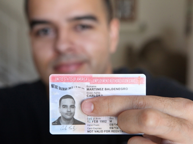 Carlos Martinez, 30, shows off his new work permit, which he received after applying for the Deferred Action for Childhood Arrivals program.