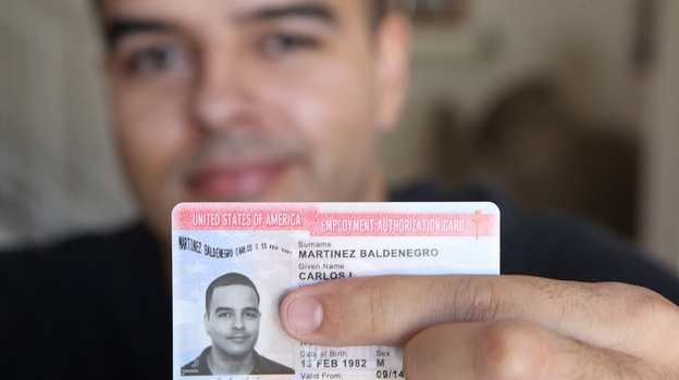 Carlos Martinez, 30, shows off his new work permit, which he received after applying for the Deferred Action for Childhood Arrivals program. (Arizona Daily Star)