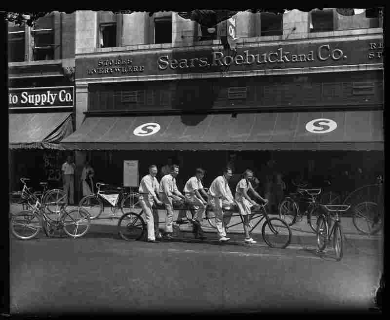 Five-person bicycle in front of Sears, Roebuck & Co., downtown Springfield, circa 1933.