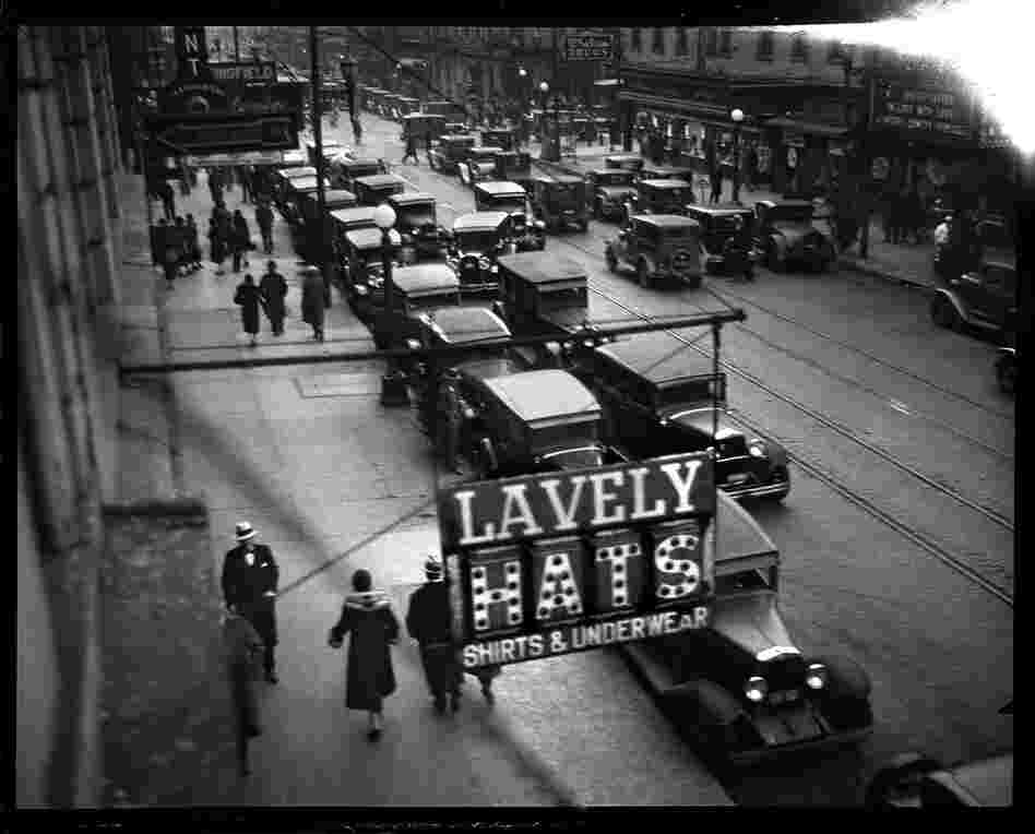 In 1930, the Illinois Power Co. operated the city's buses and streetcars and advertised regularly in the Journal, promoting the advantages of using mass transportation. The photo staff was assigned to capture street scenes that showed congestion, and their photographs were used in the ads. This image shows Monroe Street facing west from Sixth Street, December 16, 1930.
