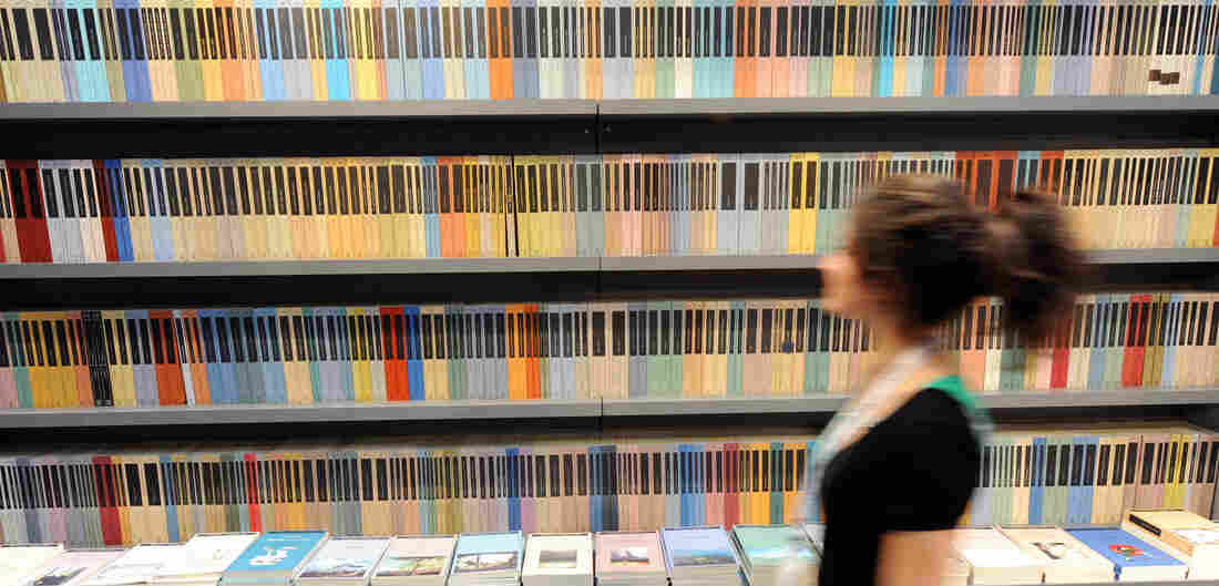 A woman walks in front of a bookshelf at Turin's book fair on May 08, 2008.