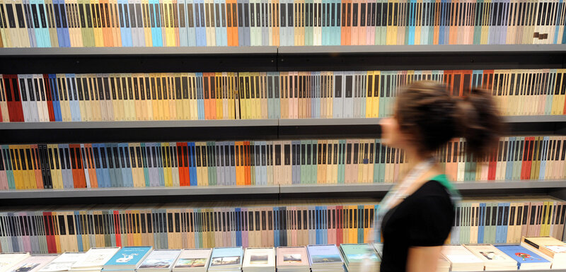 A Woman Walks In Front Of Bookshelf At Turins Book Fair On May 08