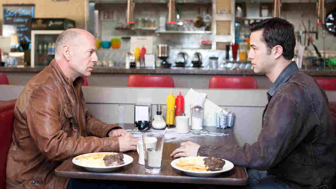 Old Joe (Bruce Willis) and his younger self (Joseph Gordon-Levitt), two iterations of the same assassin, play a particularly personal game of cat and mouse in the time-travel thriller Looper.