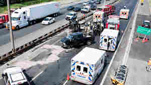 Fire department personnel, police officers and paramedics at the scene of a fatal collision on Highway 401 in Mississauga, Ontario, in July 2011.