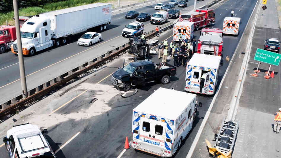 Fire department personnel, police officers and paramedics at the scene of a fatal collision on Highway 401 in Mississau