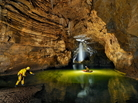 Cavers cross Lake Cadoux in a small dingy inside the Gouffre Berger cave. A 4-meter-deep (approximately 13 feet) pool of water blocks the way forward through the Starless River.