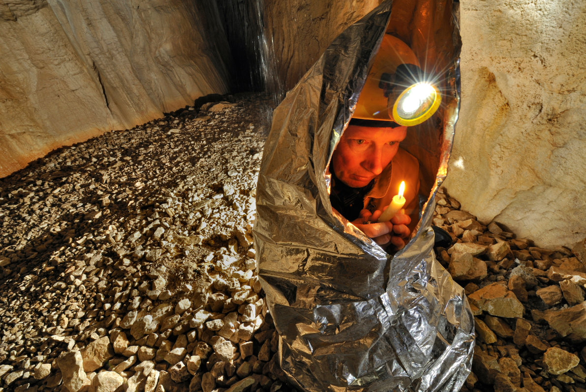 Tim Nixon tries to warm up using the heat from a candle. The temperature in the cave constantly hovers around 4 degrees Celsius (39.2 F).