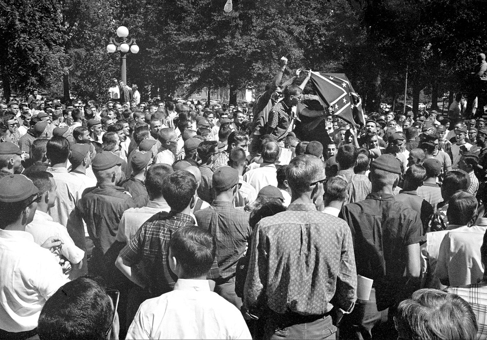 Hundreds of Ole Miss students crowd the street in front of the registrar's office, hoisting a Confederate flag and shouting for continued segregation. (AP)
