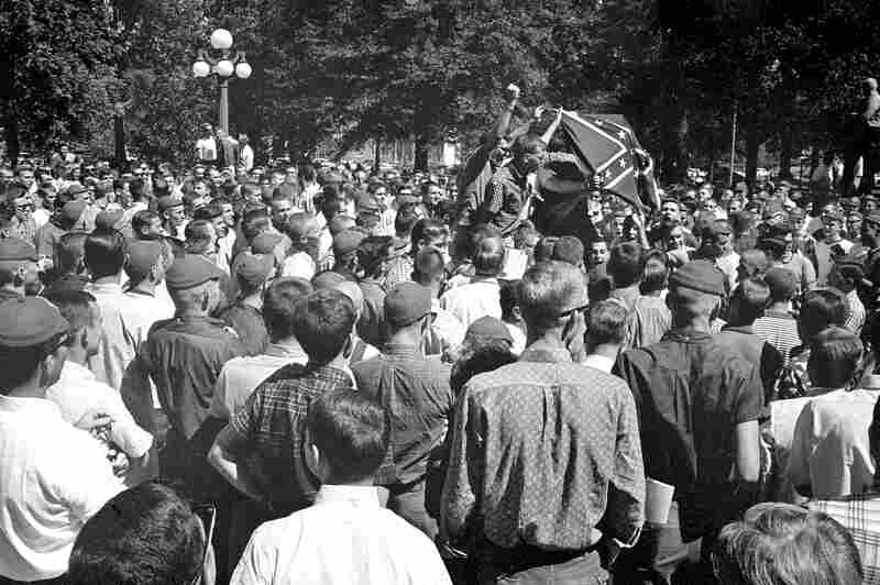 Hundreds of Ole Miss students crowd the street in front of the registrar's office, hoisting a Confederate flag and shouting for continued segregation.