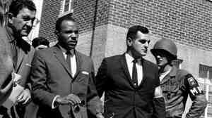 James Meredith is escorted by U.S. Marshals. A riot broke out in 1962 when Meredith tried to enroll at the University of Mississippi.