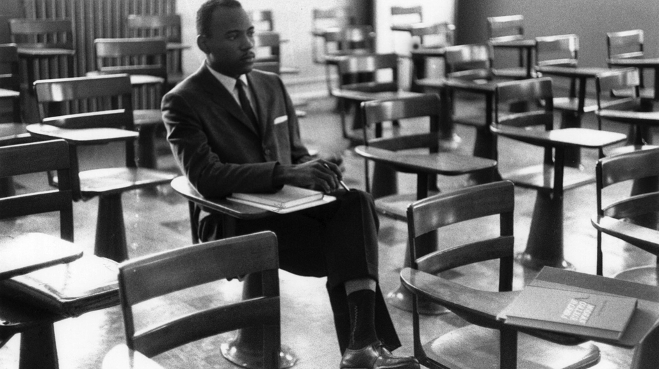 Meredith sits alone on his first day of class. A photographer who was there remembers the other students leaving the room in protest. (Courtesy of Ed Meek)