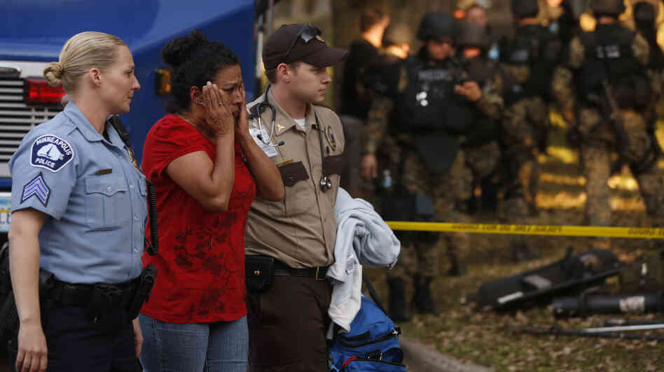 In shock: The scene outside a Minneapolis business Thursday. A gunman killed four people, wounded four others and