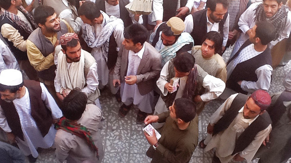 Money-changers in the Afghan city of Herat carry large stacks of Iranian currency. (NPR)
