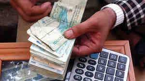 A money-changer in the Afghan city of Herat counts a stack of Iranian bills. More and more Iranian currency is being brought in by smugglers to exchange for dollars, which then go back