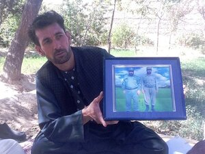 Mohammed Naeem, a driver, holds up a framed photo of two relatives he says were killed by militant leader Ab
