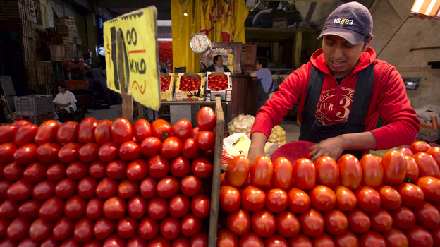 A worker separates tomatoes at a market in Mexico City. The Commerce Department says it might act to end a 16-year-old trade deal governing fresh Mexican tomatoes sold in the U.S. (AP)