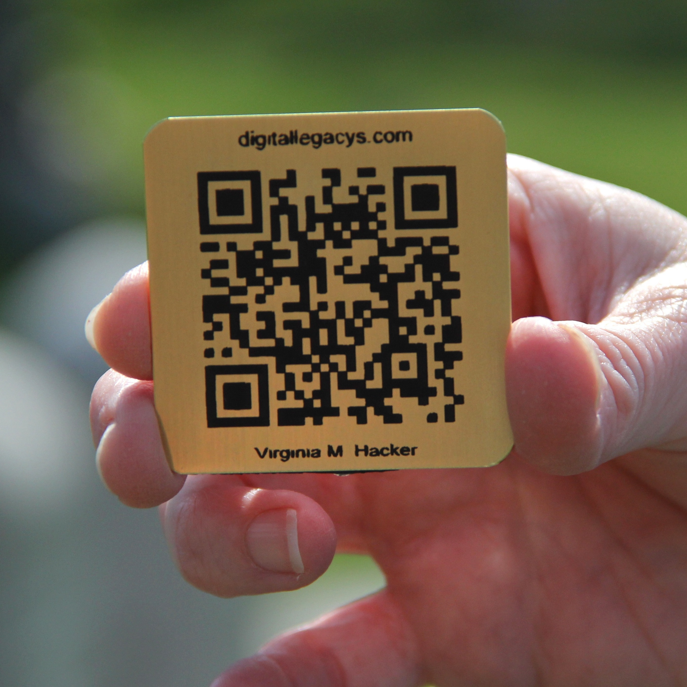Lorie Miller holds the brass QR code for her grandmother's gravestone. Smartphone users who scan it will be directed to an online tribute.